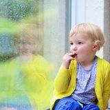 Little girl sitting next window on rainy day Royalty Free Stock Images