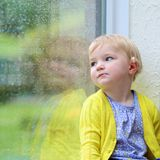 Little girl sitting next window on rainy day Stock Image