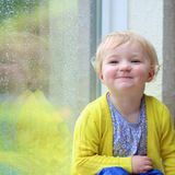 Little girl sitting next window on rainy day Stock Photos
