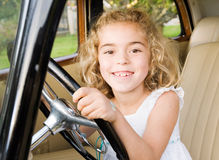 Little girl sitting in an old car and looking at camera Stock Photo