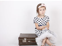 Little girl sitting on an old suitcase Royalty Free Stock Image