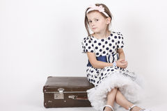 Little girl sitting on an old suitcase Stock Image