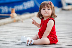 Little Girl Sitting On A Wooden Pier Royalty Free Stock Image