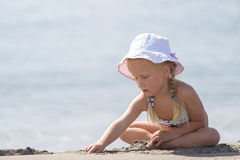 Free Little Girl Sitting On The Beach Stock Image - 64891261