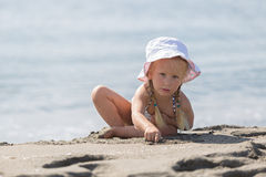 Free Little Girl Sitting On The Beach Royalty Free Stock Photos - 64891848