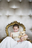 Little girl sitting in an ornate chair wearing a party dress holding a teddy bear Stock Photo