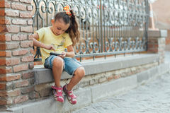 Little girl is sitting outdoor and playing on the phone Stock Photos