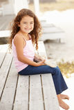 Little girl sitting outdoors holding starfish Stock Photos
