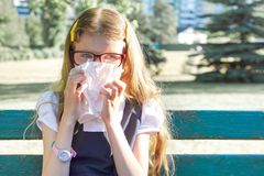 Little girl sitting in park sneezing with handkerchief, seasonal allergies royalty free stock photography