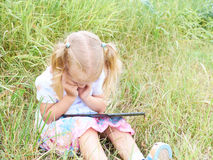 Little girl sitting in park on sunny day and play with tablet pc Royalty Free Stock Images
