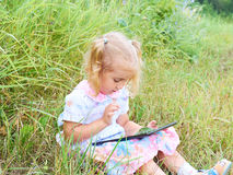 Little girl sitting in park on sunny day and play with tablet pc Stock Photos