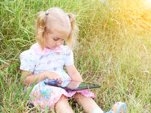 Little girl sitting in park on sunny day and play with tablet pc Stock Photo