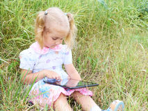 Little girl sitting in park on sunny day and play with tablet pc stock images
