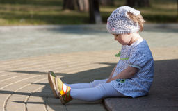 Little girl sitting on a pavement Stock Photography