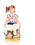 Little girl sitting on a pile of books isolated Stock Photos