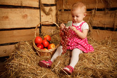 Little girl is sitting on pile with grapes Stock Photography
