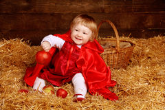 Little girl is sitting on pile of straw with apple. Little Red R Royalty Free Stock Photography