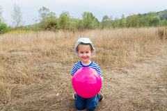 A little girl is sitting with a pink ball Stock Image