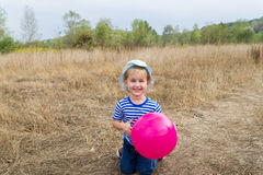 A little girl is sitting with a pink ball Royalty Free Stock Photography
