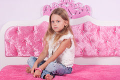 Little girl sitting on a pink bed Stock Photography