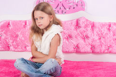 Little girl sitting on a pink bed Stock Photos