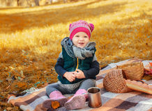 Little girl sitting on a plaid Royalty Free Stock Image