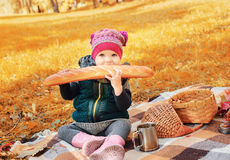 Little girl sitting on a plaid and eating a baguette Stock Images
