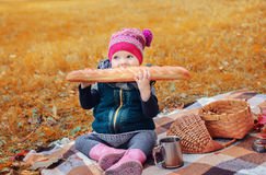 Little girl sitting on a plaid and eating a baguette Royalty Free Stock Photos