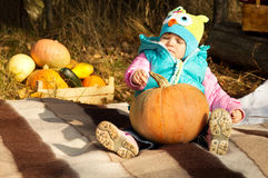Little girl sitting on the plaid with a pumpkin Stock Image