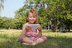 Little girl sitting play with tablet Stock Image