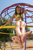 Little girl sitting at the playground on the beach Stock Photography