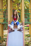 Little girl sitting at the playground in roller skates Stock Image