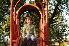 Little girl sitting on playground slide Stock Photo