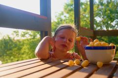 Little girl is sitting on porch in summer. Cheese balls in bowl. Cheese flavoured snacks on a table. Dreamy and romantic stock photos