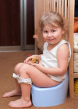 Little girl sitting on a potty royalty free stock photo