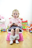 Little girl sitting on the potty. With a remote control (or mobile phone) in hand stock photo