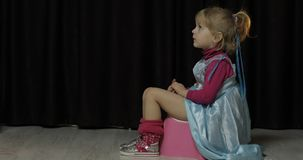 Little girl sitting on the potty and watching TV stock photography