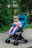 Little girl is sitting in a pram in a beautiful park. Stock Photo