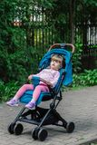 Little girl is sitting in a pram in a beautiful park. Stock Photography
