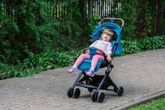 Little girl is sitting in a pram in a beautiful park. Stock Image