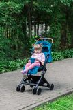 Little girl is sitting in a pram in a beautiful park. Royalty Free Stock Images