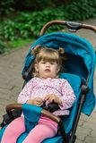 Little girl is sitting in a pram in a beautiful park. Royalty Free Stock Photo