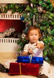 Little girl sitting with presents Stock Images