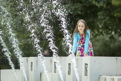 Little girl sitting on a public fountain. Royalty Free Stock Images