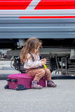 Little girl sitting at suitcase on railway station with the train on background. Little girl sitting at railway station with the train on background Royalty Free Stock Photography