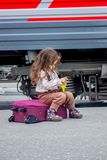 Little girl sitting at suitcase on railway station with the train on background. Little girl sitting at railway station with the train on background Stock Photography