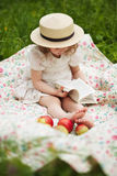 Little girl sitting and reading a book Stock Image