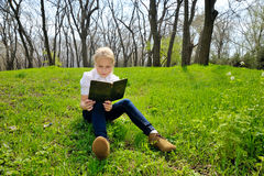 Little girl sitting and reading a book on nature. Little blond girl reading book between green spikes meadow garden Royalty Free Stock Photo