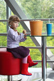 Little girl sitting on red chair at table with large portion of popcorn Royalty Free Stock Photos