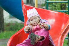 Little girl sitting on red plastic playground slide and tying shoelaces of her kids trainers Royalty Free Stock Image